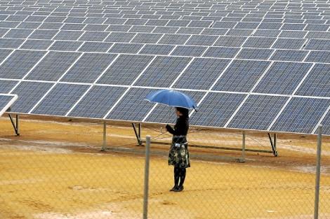 Una mujer bajo la lluvia caminando en un huerto solar, en Valencia. | Jesús Morón.