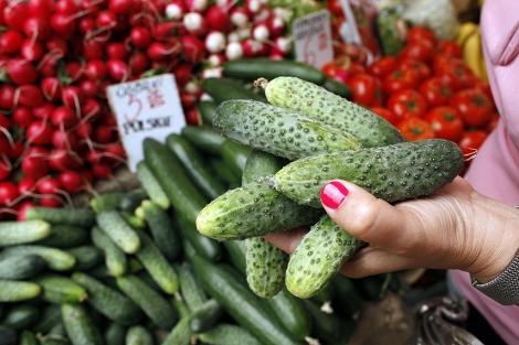 Una mujer compra pepinos en un mercado de Warsaw. | Reuters