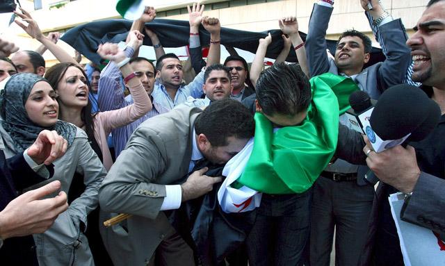 Miembros de la oposición siria besan una enseña anterior a 1980 para protestar contra el presidente Asad.   Afp