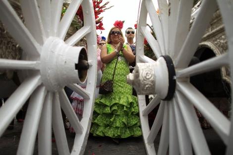 Una peregrina acompaña a la hermandad de Gines en su camino al Rocío.   Marcelo del Pozo