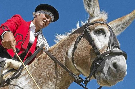 Carlos Román monta a su burro, de nombre 'Caramelo', en una exhibición. | Efe