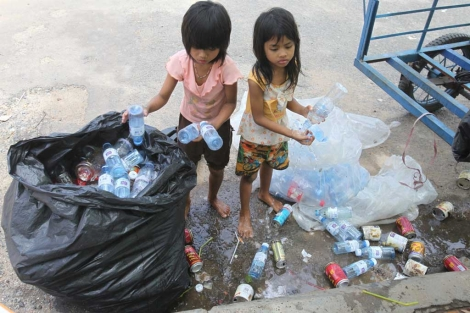 Dos niñas camboyanas recogen botellas en la calle.| Efe