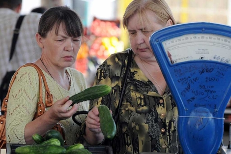 Una mujeres miran unos pepinos en Mogilev, Bielorrusia.|