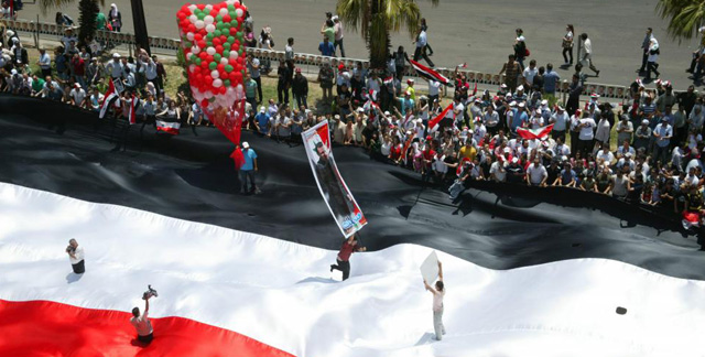 Simpatizantes de Asad sobre una gran bandera en las calles de Damasco. | Afp