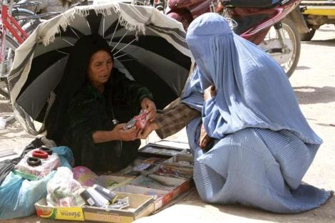 Una mujer con burka compra en un mercado de Herat. | Efe
