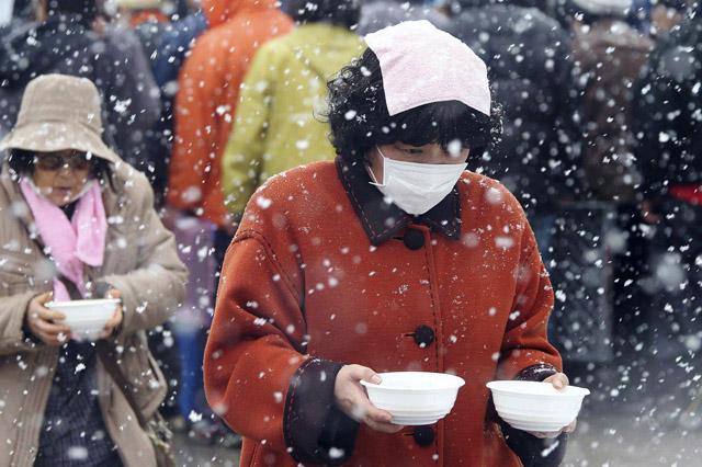 Dos mujeres evacuadas llevan cuencos de arroz a su refugio.| AP Photo