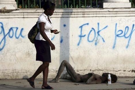 Una mujer pasa junto a una víctima del cólera en Puerto Príncipe.| Hector Retamal/AFP