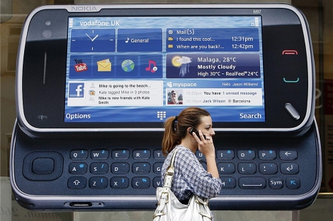 Una mujer al teléfono pasa enfrente de un anuncio de Nokia en Londres   Luke MacGregor