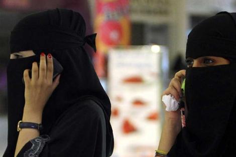 Dos mujeres saudíes hablan por teléfono móvil.| Reuters