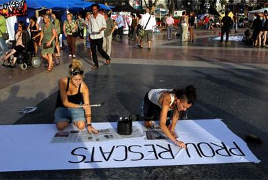 Dos 'indignadas' preparan una pancarta en la plaza de Catalunya. | D. Umbert