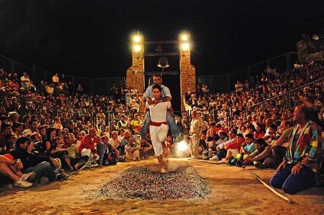 Algunos participantes cruzan la alfombra de brasas con un familiar a hombros. | D. Xygalatas.