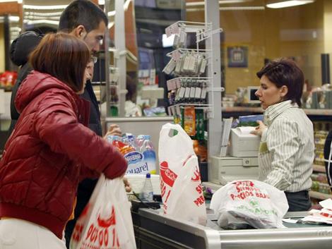 Una cajera de Mercadona atendiendo a dos clientes en Valencia.
