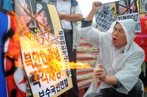 Un manifestante surcoreano quema este viernes la imagen de los líderes norcoreanos. | Afp
