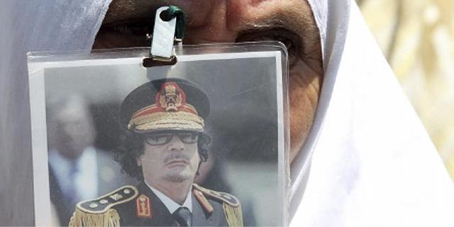 Un mujer muestra una foto de Gadafi.| Efe