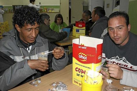 Dos personas con escasos recursos desayunan en un centro de Cáritas. | ELMUNDO.es