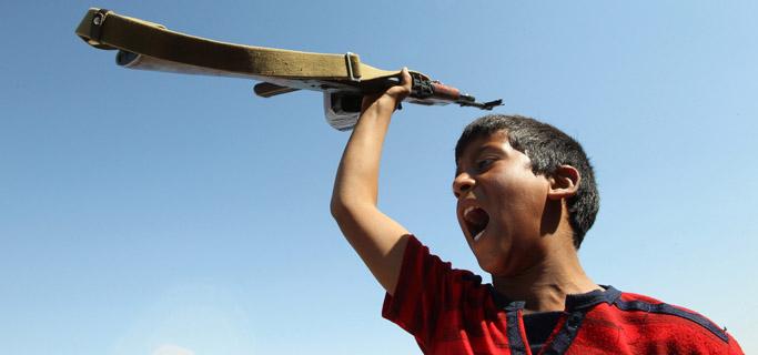 Un joven seguidor de Gadafi, grita consignas sosteniendo un rifle en Libia. | Efe