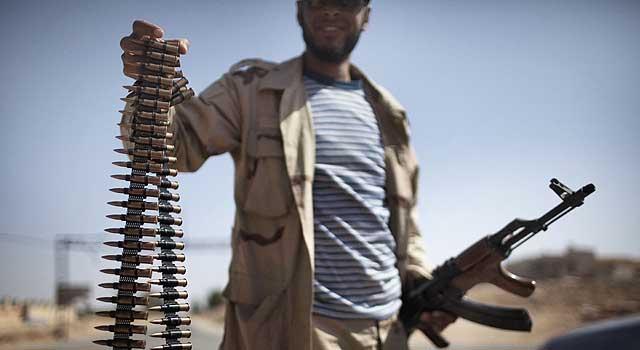 Un rebelde muestra un cinturón de balas ante la puerta oeste de la ciudad de Ghualish.   Afp