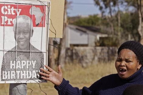 Una mujer en Sudáfrica muestra un cartel conmemorativo del aniversario de Mandela. | AP