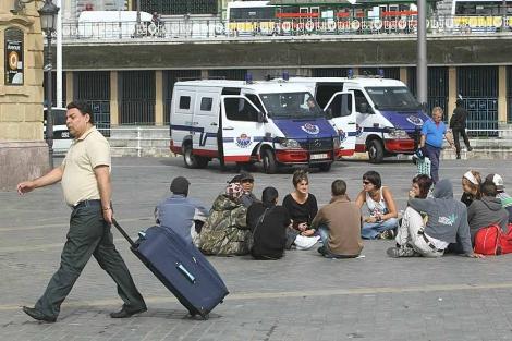 Una docena de 'indignados' sentados como protesta bajo la vigilancia de la Ertzaintza.   Mitxi