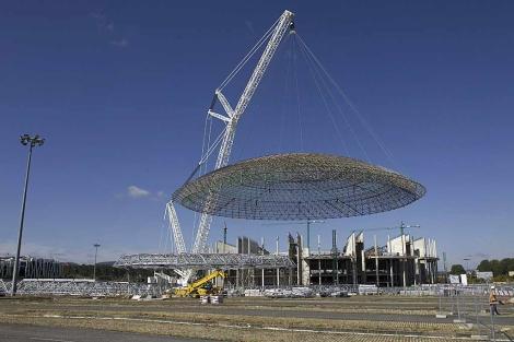 La grúa de 120 metros de altura traslada la cúpula del Buesa Arena.   Nuria González