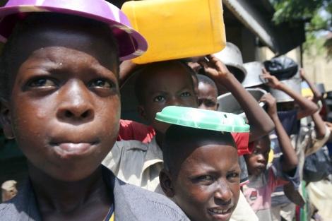 Niños somalíes desplazados internos esperan en una cola a recibir comida.| REUTERS