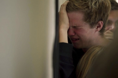 Un joven llora la pérdida de varios compañeros en el funeral. | Ap