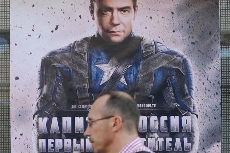 Un hombre pasa por delante de un cartel que muestra a Medvedev vestido de superhéroe.   Afp