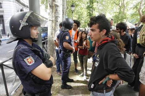 Un policía y un 'indignado' en el Paseo del Prado de Madrid .| Sergio González