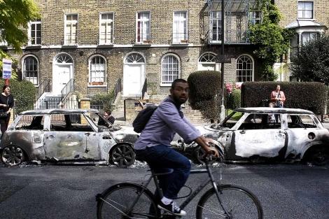 Un ciclista pasa junto a dos coches quemados en Hackney, al este de Londres.   AP