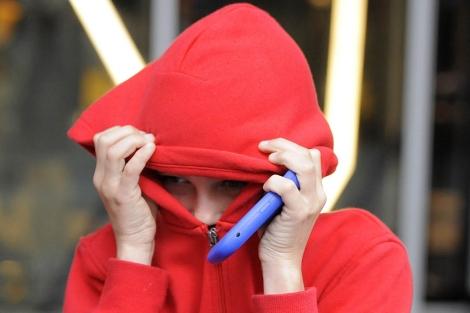 Un menor a la salida de la Magistratura de Manchester, con la capucha y su BlackBerry.|Reuters