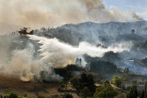 Suelta de un hidroavión sobre el incendio de Ourense, cerca de un núcleo poblado.   Efe
