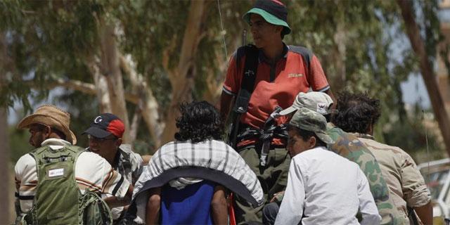 Combatientes libios rebeldes se reúnen en un puesto de control cerca de Bir Shuaib.   Reuters