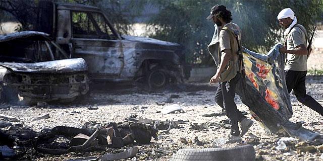 Varios combatientes acuden a cubrir un cadáver. | Reuters