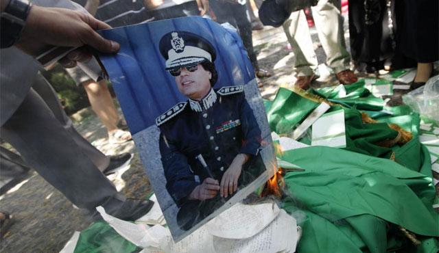 Un manifestante prende fuego a una fotografía de Muamar Gadafi. | Reuters
