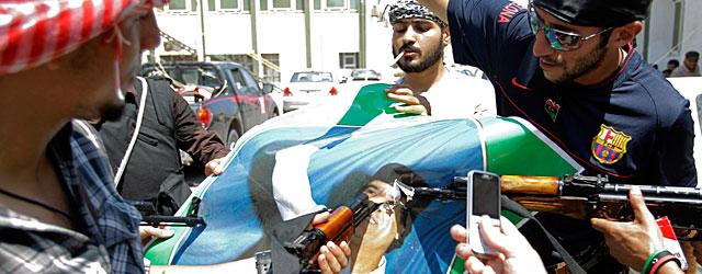 Un grupo de rebeldes destroza una foto de Gadafi en Trípoli.   Ap