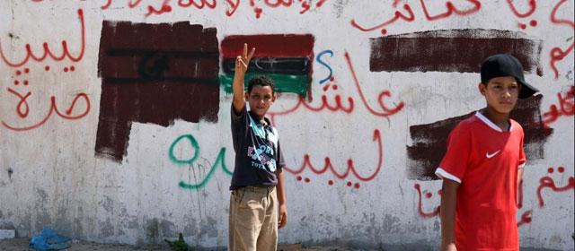 Un niño frente a una bandera rebelde libia al este de Trípoli. | Afp