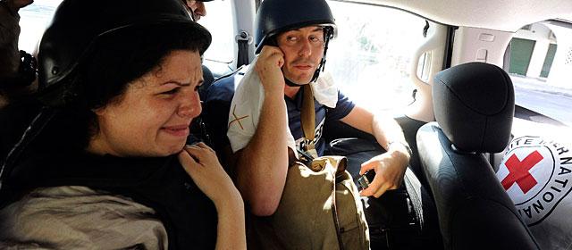 La productora Jomana Karadsheh (i) y el periodista Matthew Chance, de la CNN, son evacuados del hotel. | Reuters