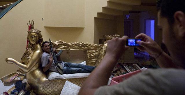Un rebelde posa sentado en el sofá con forma de sirena en la residencia de Aisha Gadafi. | AP