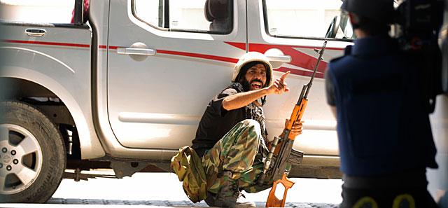 Un rebelde insta a un cámara a ponerse a cubierto en las inmediaciones del hotel Corinthia. | AFP
