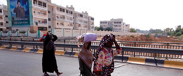 Varias mujeres huyen del centro de Trípoli ante un mural de Gadafi. | Reuters MÁS FOTOS