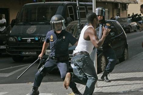 Dos agentes tratan de frenar a un nigeriano en su huida. | J. Avellà