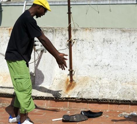 Un nigeriano muestra los zapatos del hombre fallecido en una azotea   Efe