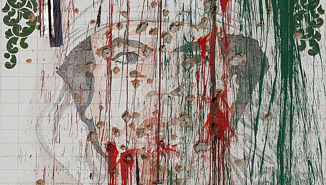 Un mural con la imagen de Gadafi llena de agujeros de bala y pintura, en Trípoli. | Ap