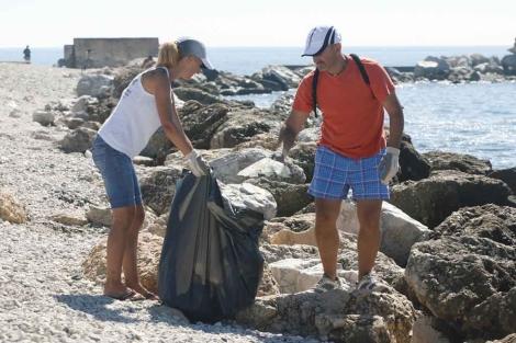 Voluntarios limpian el espigón de La Térmica. | A. Pastor