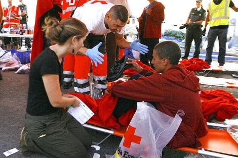 Miembros de Cruz Roja atienden a un inmigrante rescatado en Santa Pola el domingo. | Efe