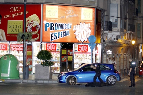 El cuerpo de la víctima, junto a un agente de Policía, en plena calle de Alicante. | Roberto Pérez