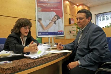 Una bancaria explica a un cliente las características de una hipoteca. | Carlos Alba