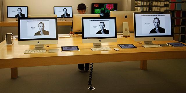 Un niño observa un ordenador con la imagen de Steve Jobs en una tienda Apple de California. | Reuters