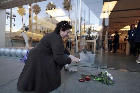 Una mujer desposita flores en una tienda de Apple en Santa Monica, California.   Reuters)