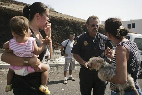 Un agente informa a vecinos de La Restinga sobre el punto de reunión. | Efe/Cristóbal García